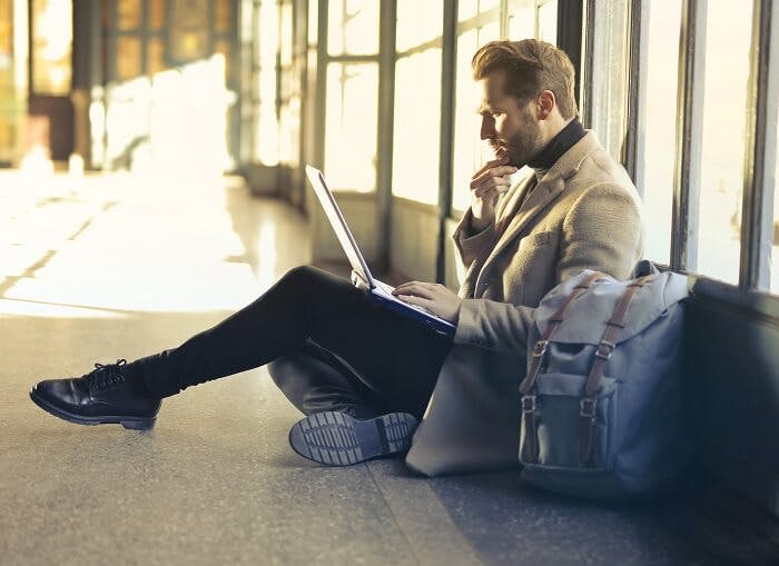 Man on laptop at airport